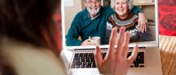 Woman speaks to older couple virtually via her laptop