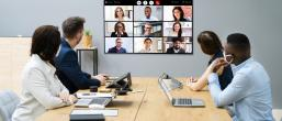 Four people sat around a table viewing a large screen of online meeting participants