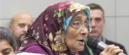 Image of woman speaking into a microphone. She is wearing a headscarf.