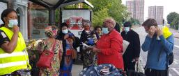 People stood at a bus stop in masks
