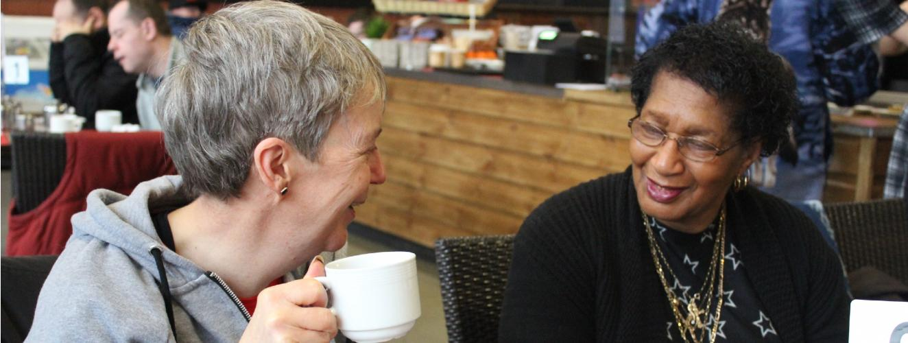 Women smiling at each other in a cafe
