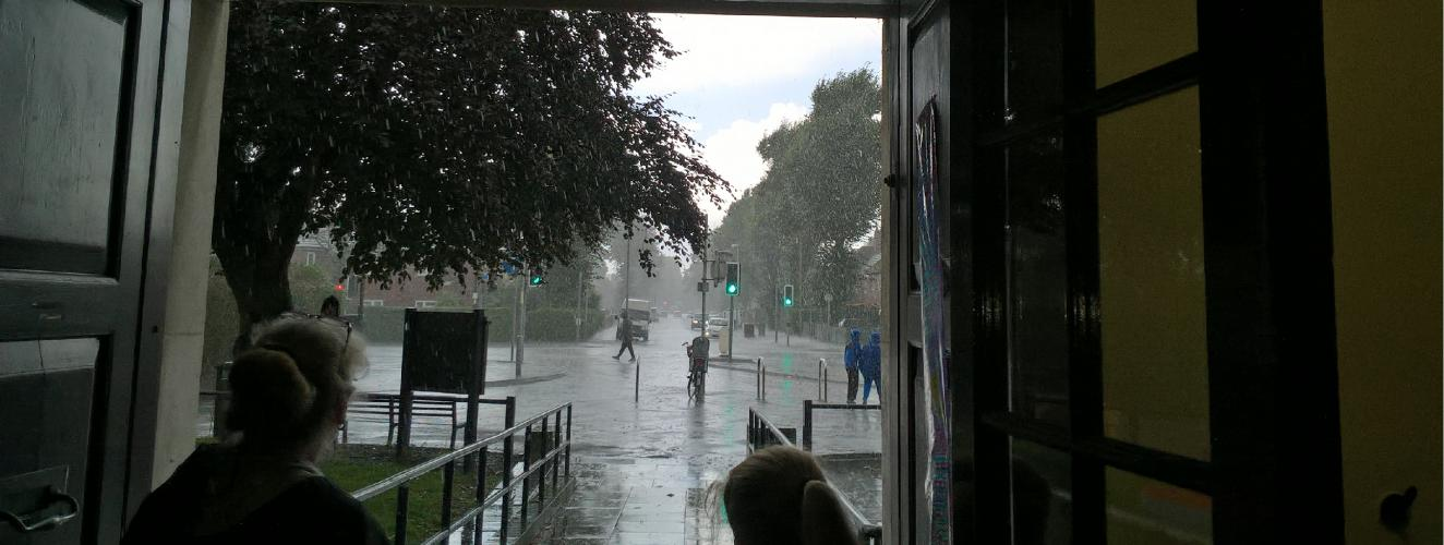 A rainy street scene from the perspective of a doorway