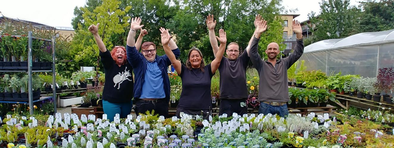 People at a garden centre with their arms in the air