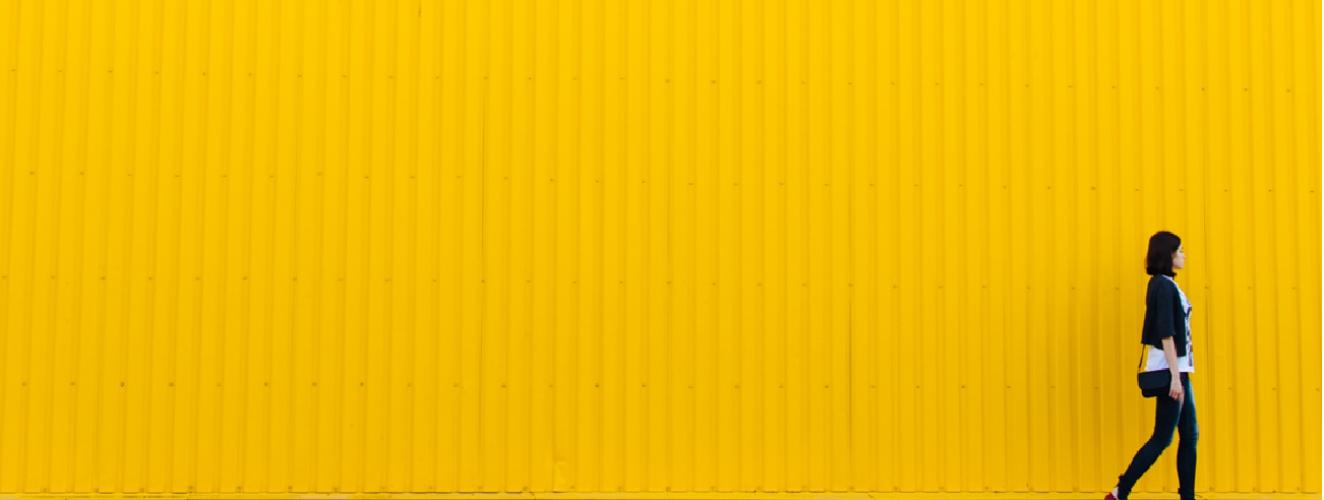 A woman walking in front of a yellow wall